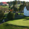 A sunny view of a green with the clubhouse in background at Meadows Farms Golf Course