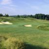 A sunny day view of a green protected by bunkers at Worthington Manor Golf Club